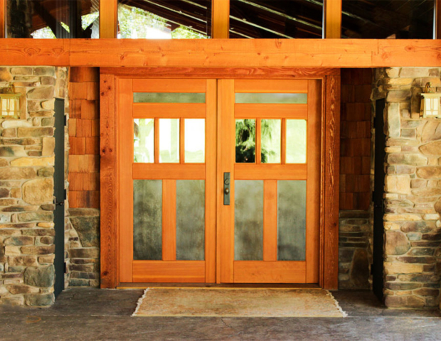 """3. """"We used stone and douglas fir timbers to transform our 1950's """"Brady Bunch"""" style ranch home to a """"lodge"""". Real Carriage doors were the finishing touches. The doors are absolutely beautiful. Everyone at Real Carriage Door helped us so much in making decisions on style, metal choices, hardware, etc. We love our """"new"""" home!"""" - Susan"""