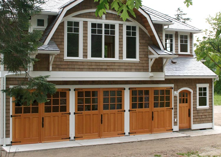 Set of 3 garage carriage doors with a pedestrian entry door made of Douglas Fir.