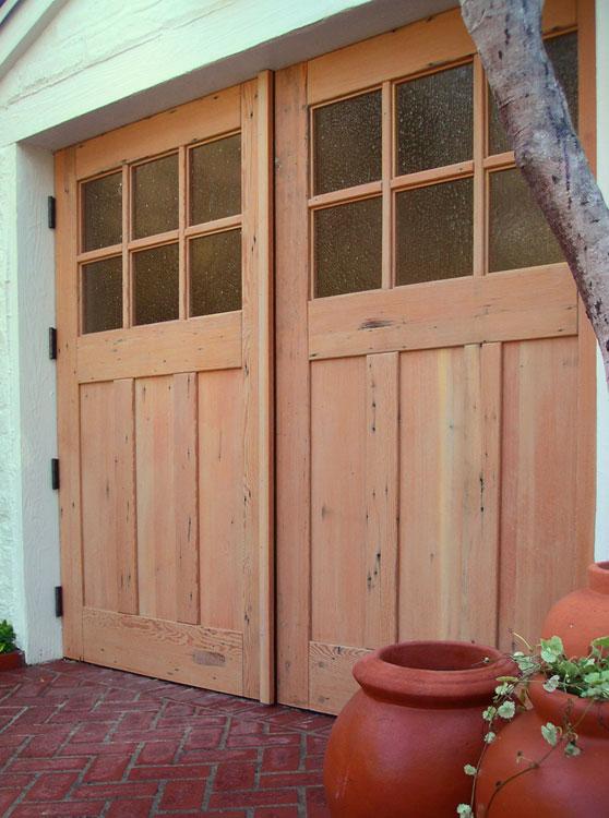 Reclaimed wood garage door that swings and has glass panels windows.