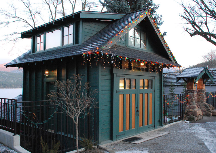 Forest green painted garage with carriage door decorated with holiday lights.