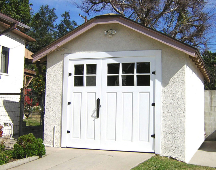 White carriage doors with black hinges and glass panels lites