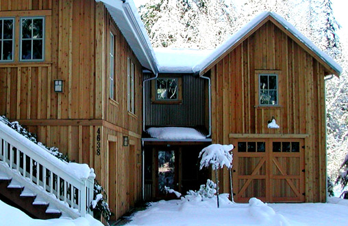 Alpine snow lodge with carriage doors made from knotty pine.