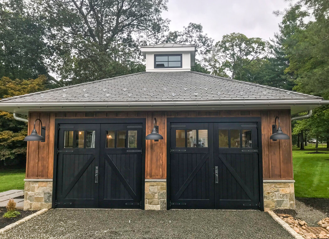 Black carriage doors on the outside of a modern carriage house garage.